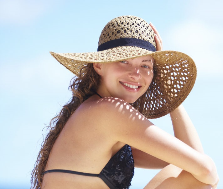 Summer vacation woman on beach in beach hat enjoying summer holidays looking at the ocean