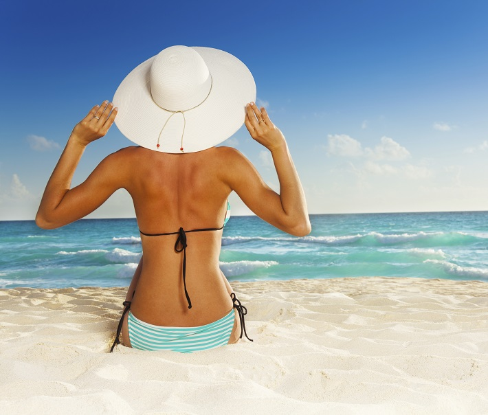 Back of beautiful girl sitting on beach in striped swimwear and white hat