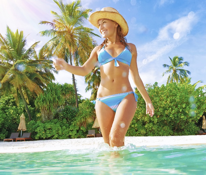 Cute slim female wearing stylish blue swimsuit comes into sea, enjoying summer vacation on Maldives island, joy and fun concept