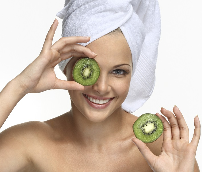 Beautiful blonde girl in towel with kiwi - on white