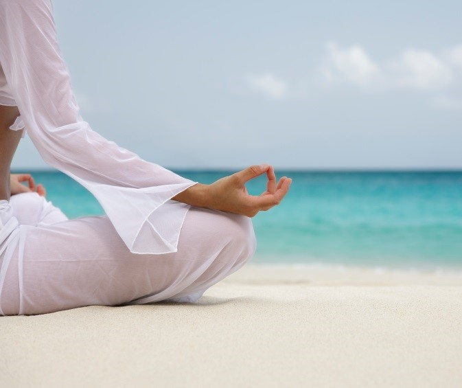 woman meditating on the beach in the Caribbean